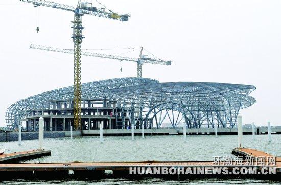 环渤海新闻网消息 在距离首都230公里的渤海湾北部海面,有几座美丽而神秘的小岛,这就是唐山湾国际旅游岛。   唐山湾国际旅游岛由菩提岛、月岛、祥云岛、星海湾及其北侧的半岛陆地组成,总规划面积约100平方公里。   图为正在建设中的总投资2.53亿元的三贝明珠码头。建筑主体远望去宛若3只巨型贝壳。赵勇摄