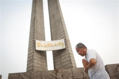 7月17日,唐山抗震纪念碑前,一位老者双手合十纪念祈福。新京报记者侯少卿摄