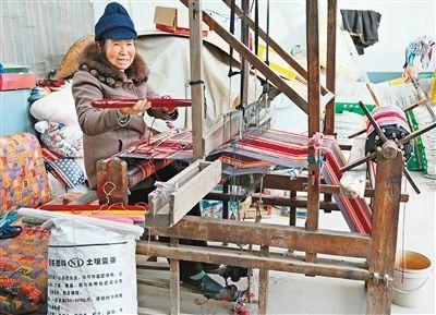 六旬农妇巧改织布机 旧毛衣变身环保床单